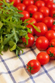 Tomatoes and arugula on towel — Stock Photo