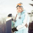 Young woman with snowboard in sunlight — Stock Photo #15523713