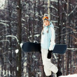 Young woman with snowboard on ski slope — Stock Photo