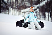 Young female snowboarder sitting — Stock Photo