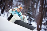 Beautiful young woman with Snowboard showing thumbs up — Stock Photo