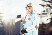 Young woman with snowboard in sunlight — Stock Photo