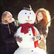 Two young women hugging snowman — Stock Photo
