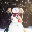 Two young women hugging snowman — Stock Photo #18608749