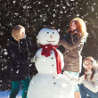 Three girls building a snowman - Stock Photo