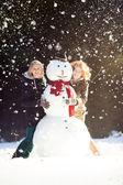 Two young women hugging snowman — Stock Photo