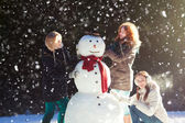 Three girls building a snowman — Stock Photo