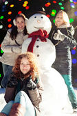 Girls and snowman — Stock Photo