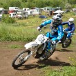 Motocross two racer  turns - Stock Photo
