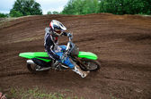 MX rider turns on a dirt hill — Stock Photo