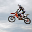 Motocross rider jumps high against the sky — Stock Photo #13818351