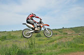Motocross rider on a motorcycle in a jump — Stock Photo