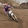 Stock Photo: Motocross party rides standing cornering furrow