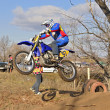 Jumping upwards rider up on a motorcycle MX - Stock Photo