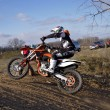 Biker rides the top of earthen the hill MX tracks - Stock Photo