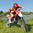 Girl sitting on sport bike, amid lakes and forests. — Stock Photo #15717879