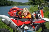 モトクロスのバイクに身を乗り出して立っている女の子です。 — ストック写真