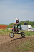 A boy on a small motorcycle motocross jumps in descent — Stock Photo