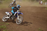 Motocross rider on motorcycle is accelerating at the exit — Stock Photo