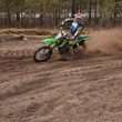 Stock Photo: MX rider turns point-blank of sand