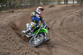 MX racer on a motorcycle in the reversal sandy track — Stock fotografie
