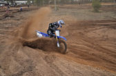 Motocross racer leaves the deep sandy ruts — Stock Photo