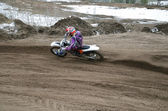 MX rider veering point-blank of sand with — Stock Photo