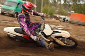 Motocross athlete raised leg forward executes turning — Stock Photo