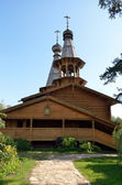 The Orthodox Church of logs with wooden domes — Stock Photo