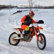 Stock Photo: Winter motocross racer on motorcycle rides in turn of