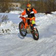 Stock Photo: Winter motocross rider riding wheelie through snow