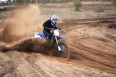 Motorcycle rider bogged down in loose sand cornering — Stock Photo