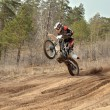 Stock Photo: MX racer standing in motion performed wheelie