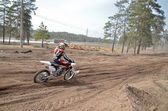 MX racer on the motorcycle accelerates on a straight section san — Stock Photo