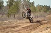 MX racer standing in motion performed a wheelie — Stock Photo