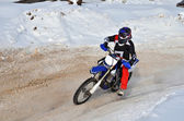 Motocross on snow racer on a motorcycle in the left turn having  — Stock Photo