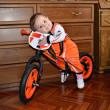 Stock Photo: Child embracing steering wheel sits on balance bike