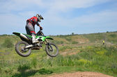 X games driver standing on the MX motorcycle is flying over the  — Stock Photo