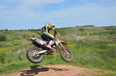 Motocross rider on a motorcycle spectacularly lands on a edge of — Foto de Stock