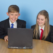 Two schoolchildren, using a computer at home — Stock Photo
