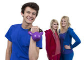 Young Man Holding Weight In Front Of Two Women — Stock Photo