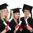 Three graduates holding scrolls — Stock Photo #26227379