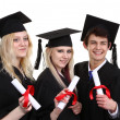 Three graduates holding scrolls — Stock Photo