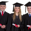 Three graduates with scrolls smiling and isolated on white — Stock Photo
