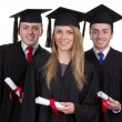 Stock Photo: Three graduate with scrolls against white background