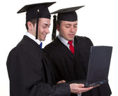 Two graduates working together on a laptop, isolated on white — Stock Photo