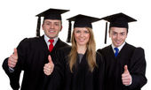 Three graduates with a thumbs up sign, isolated on white — Stock Photo