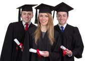 Three graduate with scrolls against a white background — Stock Photo