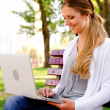 Woman resting in park and using laptop — Stock Photo