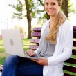Woman sitting on bench with laptop — Stock Photo #12553115